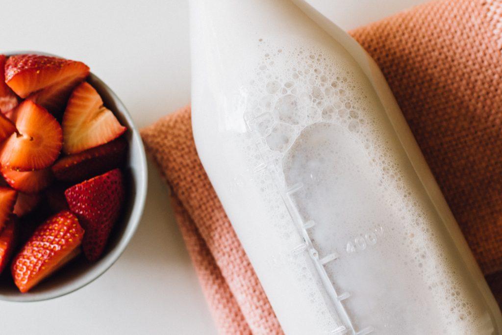 immagine di una bottiglia di latte accanto a un piatto di fragole